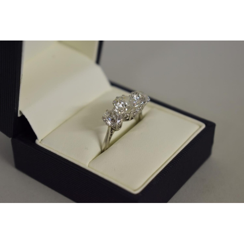 291 - <strong>An old European cut diamond and platinum three stone ring,</strong>the central stone 2.6ct,...