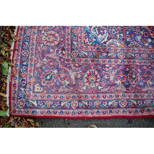 1100 - <strong>A large Persian carpet,</strong>having central floral medallion on a red and blue grou...
