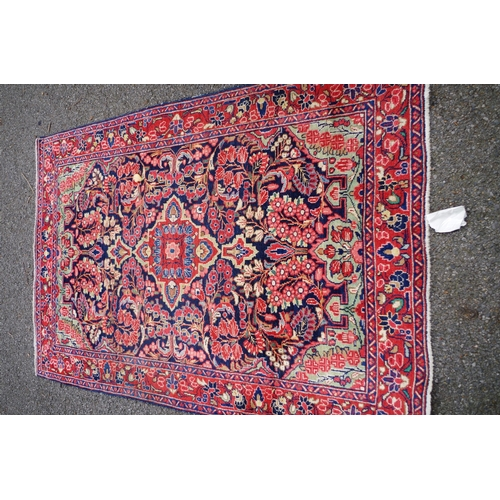 1103 - <strong>A Persian rug, </strong>having urn design to central field; together with another simil...