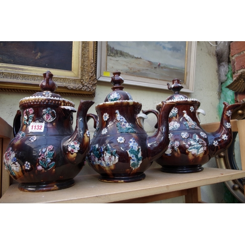 1132 - <strong>Three Victorian Bargeware teapots and covers,</strong>largest 32cm high, (each s.d.)....