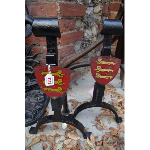 1110 - <strong>A pair of wrought iron fire dogs,</strong>each with painted shield, 49.5cm high....