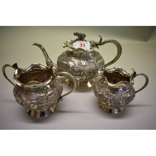 31 - <strong>An Indian white metal three piece teaset,</strong> heavily decorated with native scenes, hav...