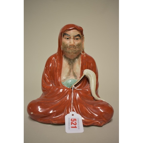 521 - <strong>A Japanese porcelain seated figure of Bodhidharma,</strong> <em>Meiji</em>, 21.5cm high....