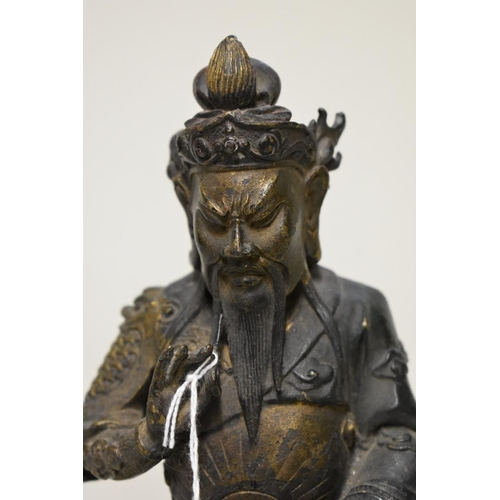 523 - <strong>A Chinese bronze seated figure,</strong> with remains of painted and gilt decoration, 21.5cm...