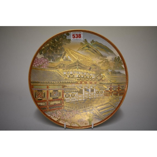 538 - <strong>A Japanese Satsuma pottery plate,</strong> <em>Meiji</em>, painted with a temple, 25cm diame...