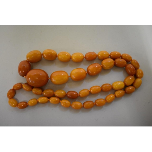 579 - <strong>A 'butterscotch' amber bead necklace, </strong>of forty three oval graduated beads, largest ...