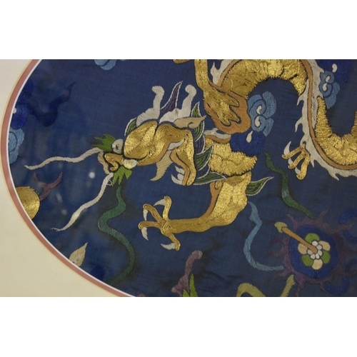 597 - <strong>A Chinese embroidered silk dragon panel, </strong>with gilt thread detail, probably from a r...
