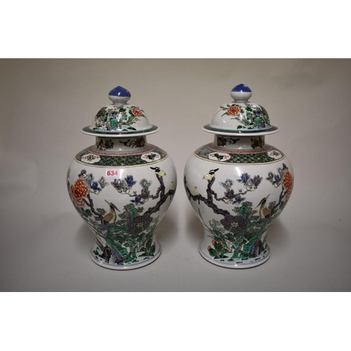 634 - <strong>A large pair of Chinese famille verte inverted baluster vases and cover</strong>, <em>Qing</...