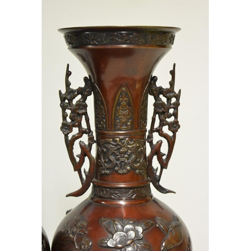 636 - <strong>A pair of Japanese bronze twin handled vases,</strong> <em>Meiji</em>, relief decorated...