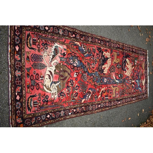 1107 - <strong>An Eastern rug,</strong>having animal motifs on a red field, with floral borders, 320 x 127...