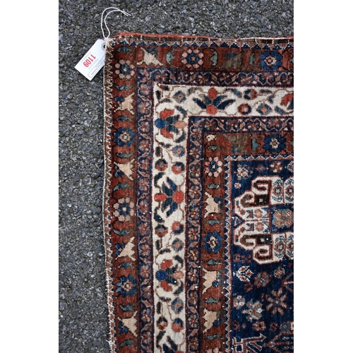 1109 - <strong>An Eastern rug, </strong>having floral and geometric design on a red and blue field, 196 x 1...