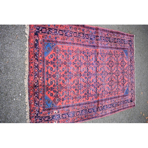 1117 - <strong>An Eastern rug, </strong>with geometric and floral design on a red field, 195 x 138cm....