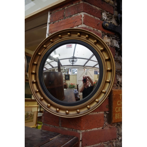1129 - <strong>A reproduction gilt framed convex wall mirror,</strong> 41.5cm diameter....