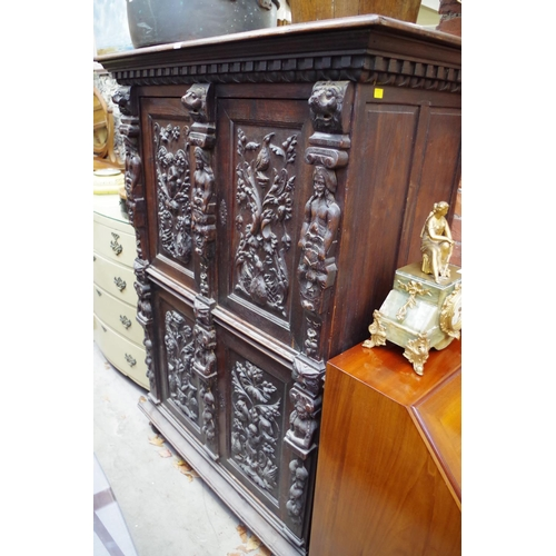 1130 - <strong>An antique Continental carved oak press cupboard, </strong>117cm wide....