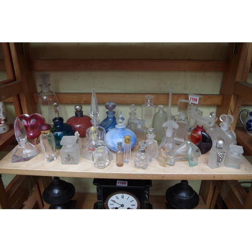 1159 - <strong>A collection of clear and coloured glass scent bottles and stoppers.</strong>...
