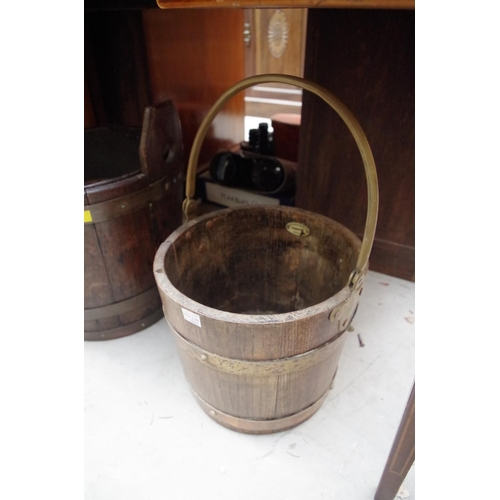 1222 - <strong>A coopered oak bucket;</strong> together with another swing handled example; and another sma...