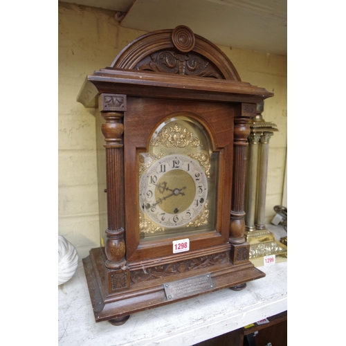 1298 - <strong>An Edwardian carved walnut mantel clock,</strong> striking on gongs, 46.5cm high, with pendu...