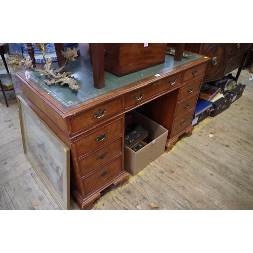 1481 - <strong>A reproduction walnut pedestal desk,</strong>124.5cm wide....