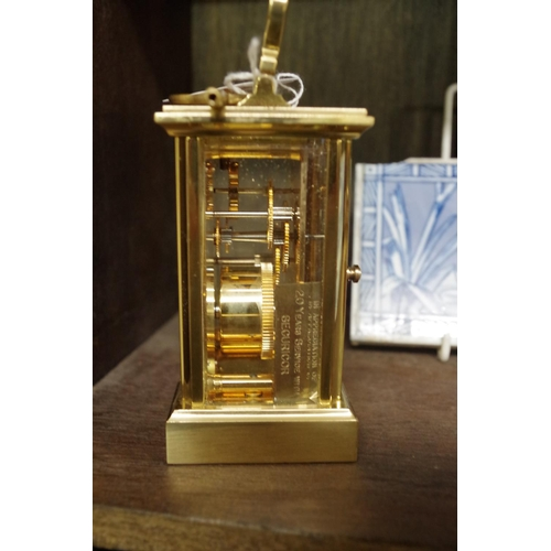1549 - <strong>A brass carriage timepiece,</strong>height including handle 15cm, with winding key.&nb...