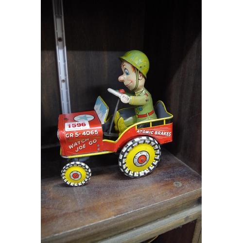 1596 - <strong>A vintage tin plate clockwork 'GI Joe Jouncing Jeep' toy.</strong>...