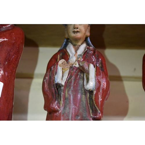 506 - <strong>Three Chinese Shiwan flambe figures,</strong> comprising: a Daoist, 30cm high; and a pair of...