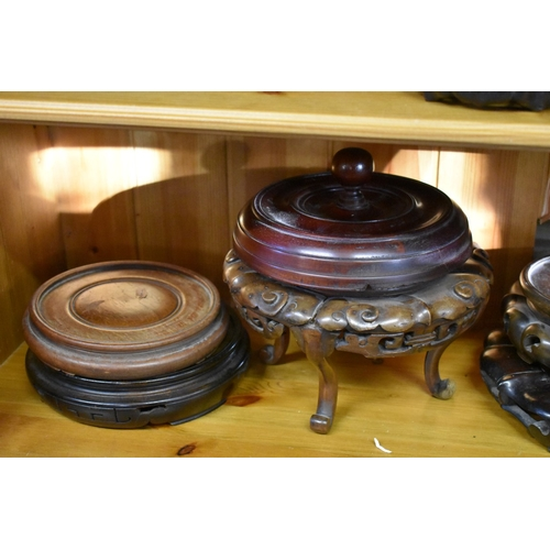 620 - <strong>A collection of fourteen Chinese hardwood stands;</strong> together with another part stand;...