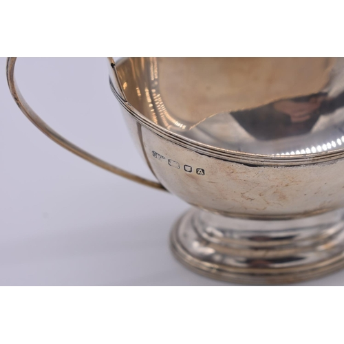 4 - <strong>A silver sauce boat,</strong> by <em>Carrington & Co,</em> London 1936, 9cm high, 1...