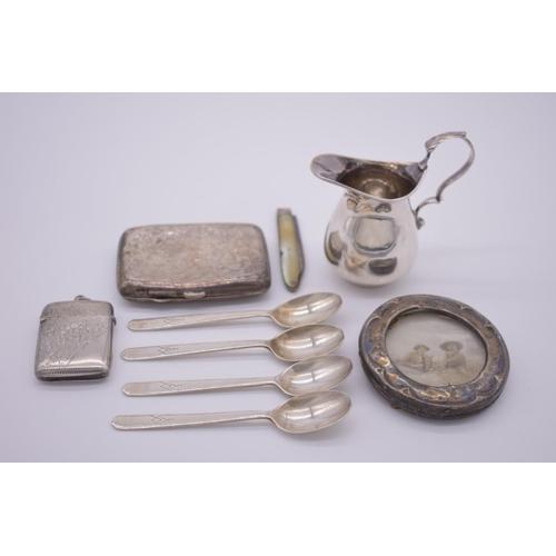 45 - <strong>A small parcel of silver items,</strong> to include: a cream jug; a circular frame; four tea...