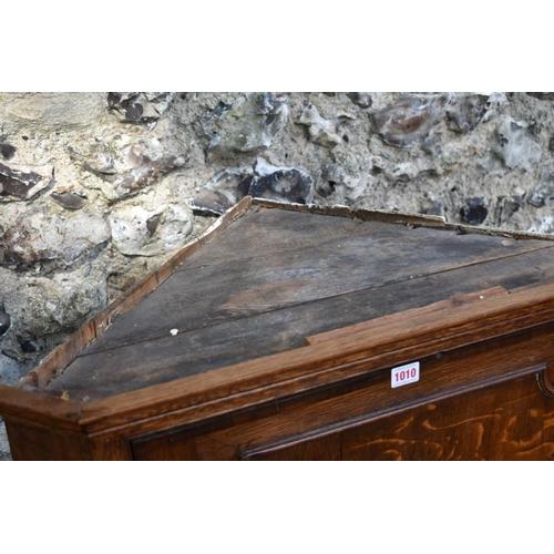 1010 - A George III oak and crossbanded mahogany hanging corner cupboard, the door enclosing shaped shelves...