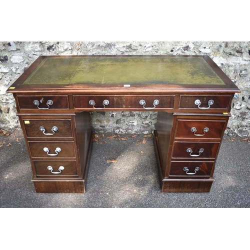 1011 - A reproduction mahogany veneered kneehole desk, having green leather inset top, 123cm wide. <st...