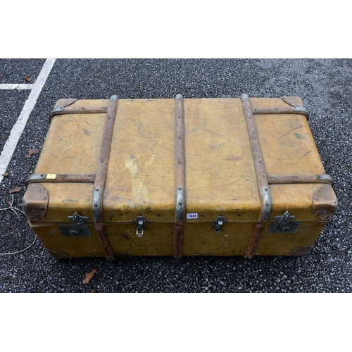 1044 - A wood bound travelling trunk, containing an Eastern prayer mat and three umbrellas.<strong>This lo...