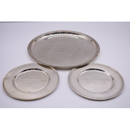 131 - <strong>Two white metal dishes,</strong> stamped 900, both engraved presentation; together with a si...