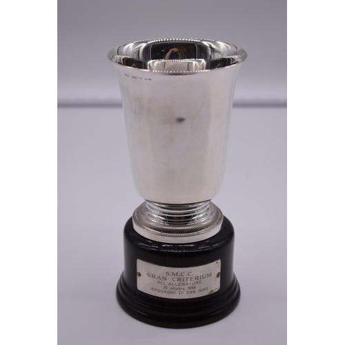 141 - <strong>An Italian white metal trophy cup,</strong> by<em> R Miracoli,</em> stamped 800, on wood soc...