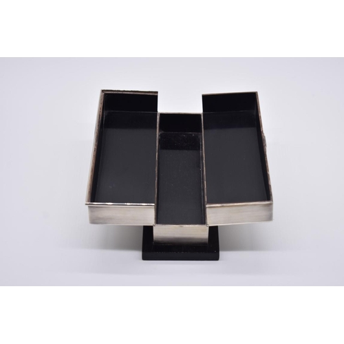 38 - <strong>An Art Deco sterling silver hinged playing card box,</strong>on ebonised base, 22cm wide....
