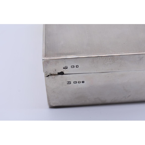 42 - <strong>An engine turned silver rectangular cigarette box, </strong>by <em>William Comyns & Sons...