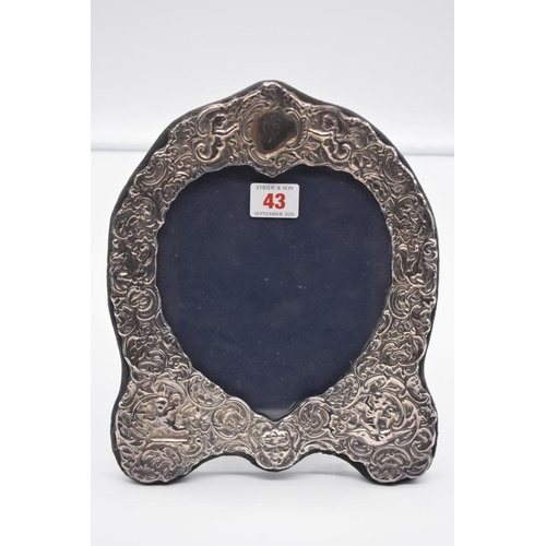 43 - <strong>An embossed silver easel back photograph frame, </strong>by <em>D R & S, </em>London 198...