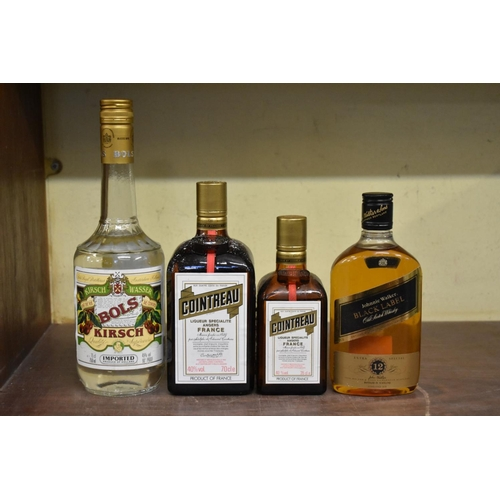 599 - <strong>A mixed lot of spirits,</strong> comprising: a 70cl bottle of Cointreau; a similar 35cl bott...