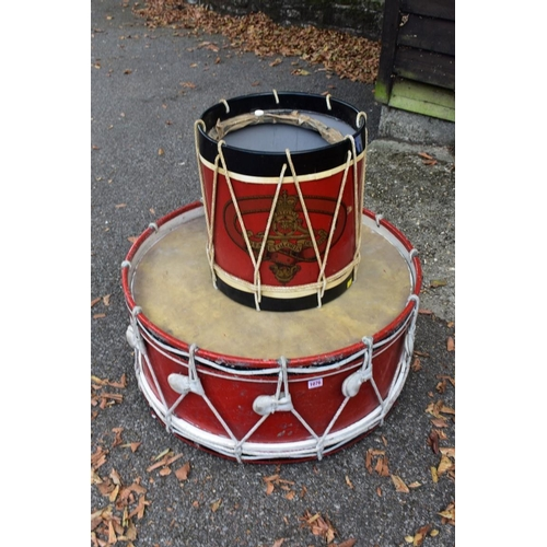 1076 - A large red painted drum, 73cm wide x 36cm high; together with a smaller example.<br /><strong>This ...