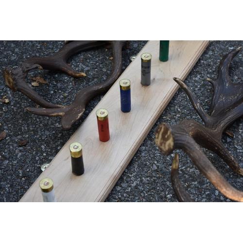 1078 - A coat rack with 'shotgun cartridge' hooks; together with a similar bullet key hook, hoof coat rack ...
