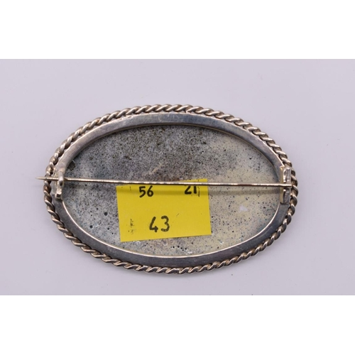 1715 - <strong>A Continental painted enamel oval plaque,</strong>in white metal brooch mount, 17.5cm wide....