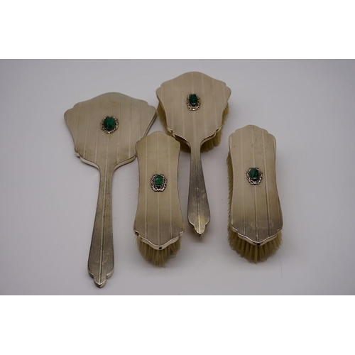 128 - A Continental four piece .800 dressing set, decorated malachite cartouche to centre....
