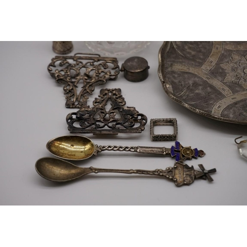 129 - A quantity of silver and other metal items, to include: a silver nurses belt buckle; a Madeira bottl...