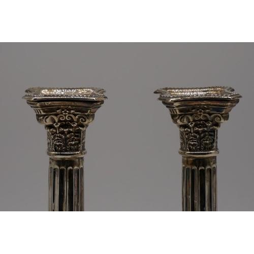 13 - <strong>A pair of silver Corinthian column candlesticks,</strong> by <em>Britton,</em> <em>Gould &am...