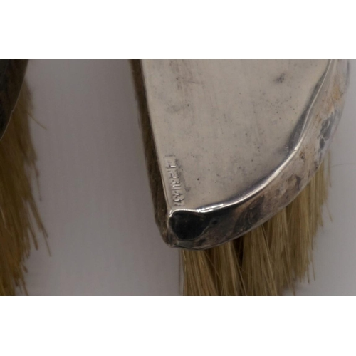 130 - Three silver mounted brushes; together with a silver handled button hook.