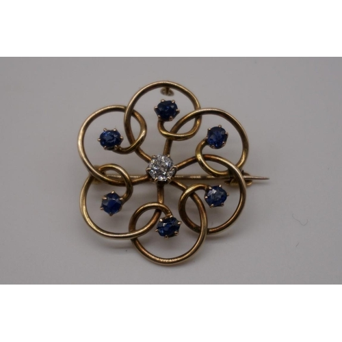 141 - A diamond and sapphire yellow metal brooch/pendant, the central diamond approximately 0.25ct, 5.4g g...