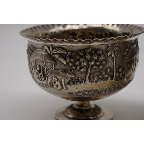 47 - <strong>A pair of Indian white metal pedestal bowls, </strong>decorated village scenes, 8.5cm high....