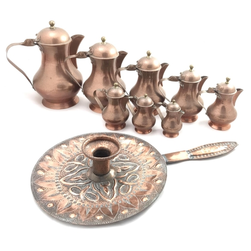 14 - Late 19th C copper arts and crafts style chamber stick C1893 L14ins plus eight numbered copper jugs...