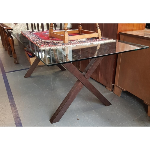 44 - Large contemporary design glass top dining table on cross wood supports L79ins W36ins...