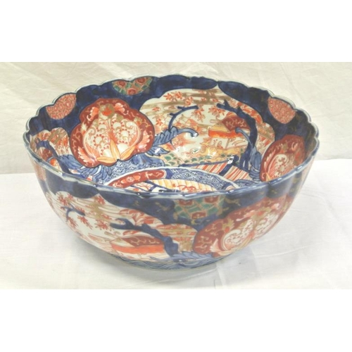 103 - Imari circular bowl with scalloped rim, burnt ochre and deep blue foliate and scenic decorated panel...