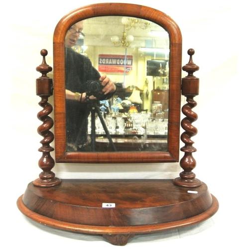 43 - Victorian walnut and mahogany framed swivel mirror with barley twist columns and shaped base...